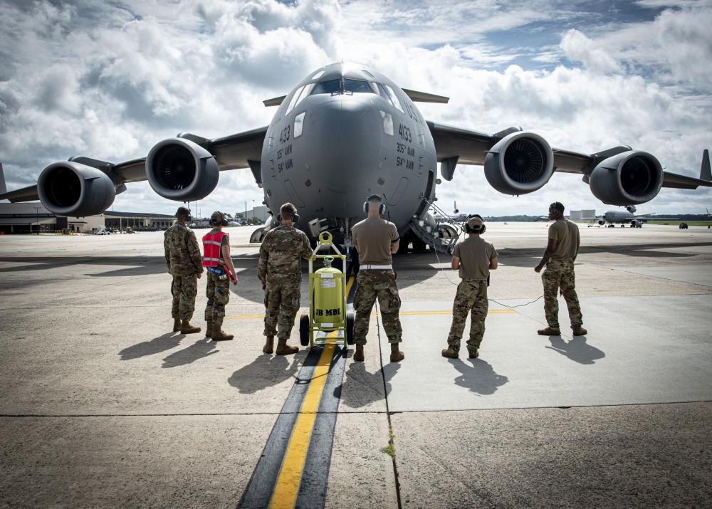 """Airmen assigned to the 305th Maintenance Group prepare to launch a C-17 Globemaster III assigned to the 305th Air Mobility Wing at Joint Base McGuire-Dix-Lakehurst, N.J., Aug. 18, 2021. The 305th AMW is responsible for delivering Rapid Global Mobility to the U.S. and its allies throughout the world. The unit's C-17 fleet was relocated to support operations in Kabul, Afghanistan. (U.S. Air Force photo by Airman 1st Class Azaria E. Foster) Joint Base McGuire-Dix-Lakehurst is playing a major role in the ongoing noncombatant evacuation operation from Afghanistan, and it will soon play host to refugees who are being transported to the United States following the fall of the government to the Taliban militant group. The base's C-17 transports could be seen on flight tracking software making up a significant portion of the massive air bridge created by allied nations to facilitate the contingency operation at Hamid Karzai International Airport. The USAF planes involved in the operation are primarily flying under variations of the callsigns """"Moose"""" and """"RCH."""" Photos from Afghanistan show U.S. Marines unloading supplies and preparing the aircraft for evacuation operations. The C-17 has become an emblem of the evacuation, first for disturbing images of Afghan civilians clutching the landing gear during takeoff before falling from the sky, and later for the iconic photograph of 800 evacuees airborne and out of harm's way. European militaries have been using their smaller Airbus A400M planes in the same role. U.S. Marines load onto a U.S. C-17 Globemaster from McGuire Air Force Base to be transported to Afghanistan on August 18, 2021, from Ali Al Salem Air Base, Kuwait. (USAF Photo) U.S. Marines load onto a U.S. C-17 Globemaster from McGuire Air Force Base to be transported to Afghanistan on August 18, 2021, from Ali Al Salem Air Base, Kuwait. (U.S. Air Force photo by Staff Sgt. Ryan Brooks) On Monday, it was confirmed that the Joint Base would be one of four bases in the Unite"""
